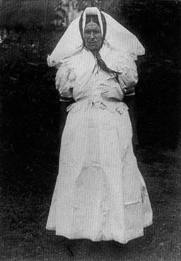 54563b69b6 Idős asszony fehér vászonruhában, pacsában.